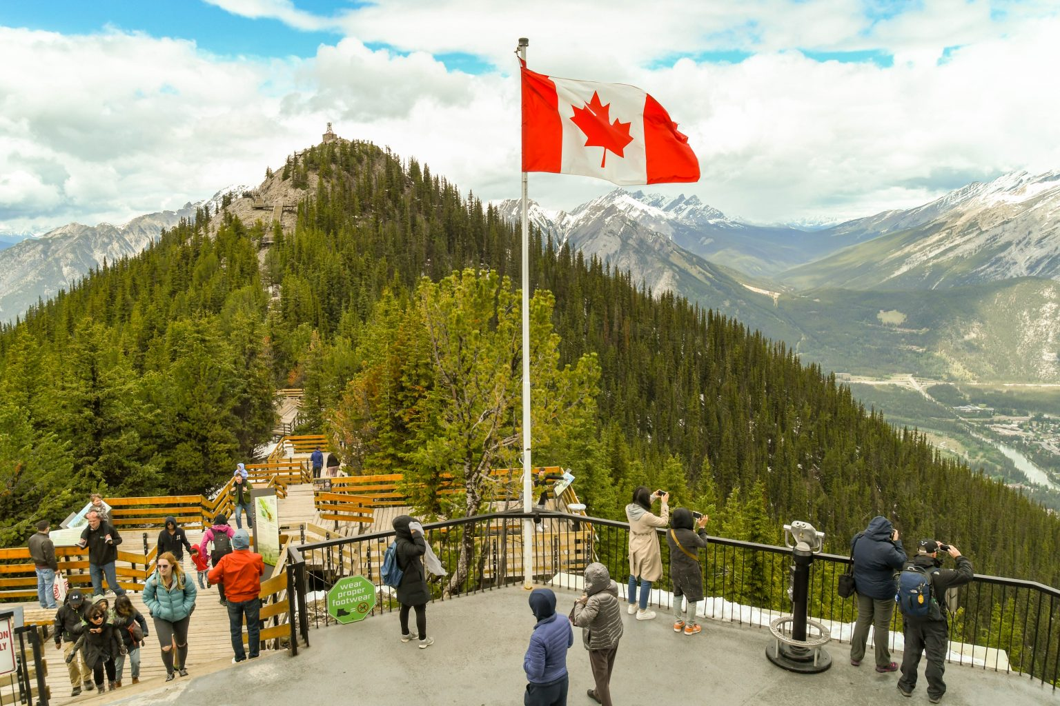 BANFF, AB, CANADA - JUNE 2018: Visitors on the lookout point on the top of Sulphur Mountain in Banff.